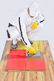 Worker applies ceramic tiles on wooden floor with notched trowel — Stock Photo