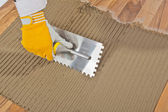 Worker applied tile adhesive on old wooden floor — Stock Photo