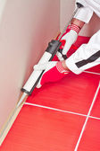 Worker applies silicone sealant on corner wall tiles — Stock Photo