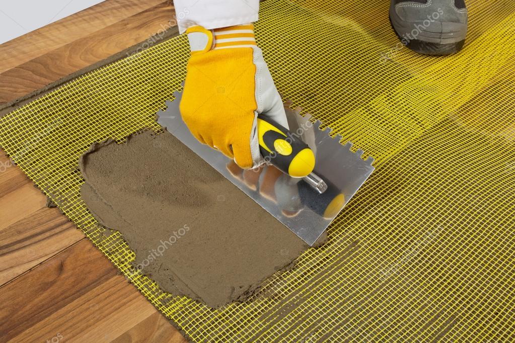 Applique la colle à carrelage sur un plancher en bois avec grillage — Photographie csimagemakers ...