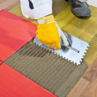 Stock Photo: Worker apply ceramic tiles on wooden floor mesh trowel