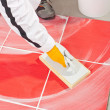 Worker clean with sponge trowel tile joints grout — Stock Photo #12060983