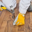 Worker nailed old wooden floor cracks - Stock Photo