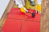 Pracovník platí s gumovou hummer dlaždice na dřevěnou podlahu — Stock fotografie