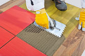Worker apply ceramic tiles on wooden floor mesh trowel — Stock Photo