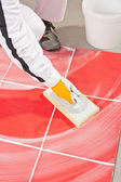 Worker clean with sponge trowel tile joints grout — Stock Photo