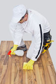 Worker cleans with sponge and spray wooden floor before tilling — Stock Photo