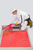 Worker cut ceramic tile machine tiling joint crosses — Stock Photo