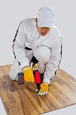 Travailleur forés fissures du plancher en bois — Photo