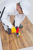 Worker drills a screw wooden floor cracks — Stock Photo