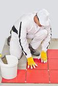 Arbetare med hink självhäftande tillämpa rött kakel — Stockfoto