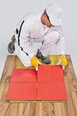 Worker applies ceramic tiles on wooden floor with fiber mesh — Stock Photo