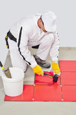 Worker Applies with Rubber Hummer Red Tile on a Floor — Stock Photo