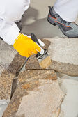Worker brush primer grout of stones joint — Stock Photo