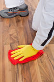Worker cleans with towel wooden floor before tilling — Stock Photo