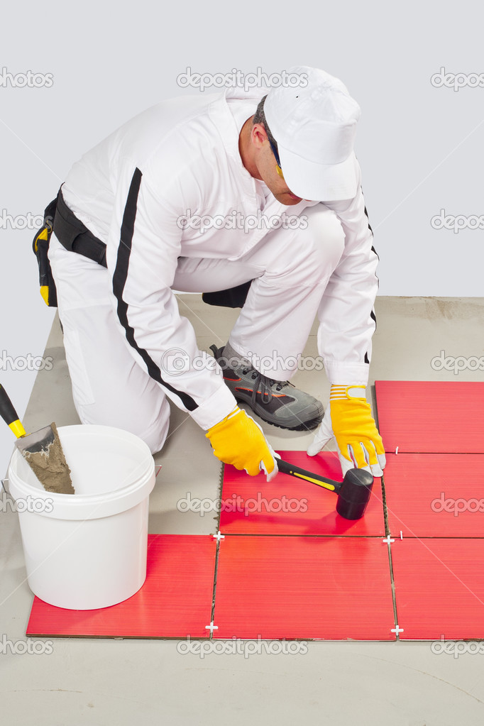 Worker Applies with Rubber Hummer Red Tile on a Floor — Stock Photo #13569107
