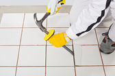 Worker with hammer removes old white tiles from floor — Stock Photo