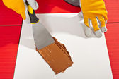Worker with trowel check on white paper mixing grout — Stock Photo