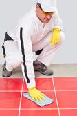 Worker with yellow gloves blue towel clean red tiles grout — Stock Photo