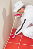 Worker wrapped with masking tape red tiles — Stock Photo