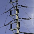 High voltage post against blue sky — Stock Photo