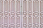 Pink metal grille sliding door with pad lock and aluminium handl — Stock Photo