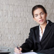 Businesswoman writing letter at desk — Stock Photo