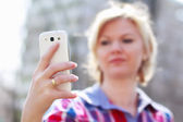 Blonde woman holding smartphone and reading — Stockfoto