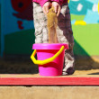 Little girl scattering sand — Stock Photo