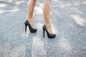 Vrouwelijke hoge hakken rode schoenen op de weg — Stockfoto