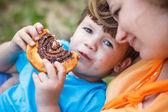 Cute boy eating chocolate snail — Stock Photo