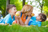 Family eating apple in the nature — Stock Photo