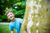 Young boy hiding at tree — Stock Photo