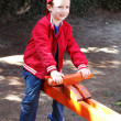 Cute boy in cap on seesaw — Stock Photo