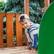 Young boy in cap climbing on playground — Stock Photo