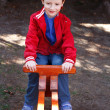 Little boy in cap sitting on seesaw — Stock Photo