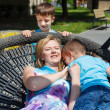 Happy family playing in saucer swing — Stock Photo