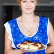 Blonde woman holding tarts with jam on plate — Stock Photo