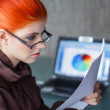 Redhead businesswoman with glasses reading document — Stock Photo