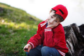Cute child sitting at river in red cap — Stock Photo