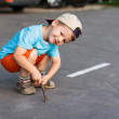 Little active boy in cap with branch — Stock Photo