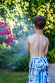 Little preschooler boy irrigate in garden — Stock Photo