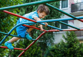 Little boy climbing on jungle gym without rope and helmet — Stock Photo