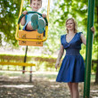 Little son swing with mother at park — Stock Photo