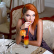 Sexy redhead woman drinking juice in restaurant — Stock Photo