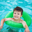 Happy young boy in pool with saver — Stock Photo