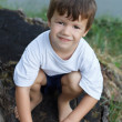 Stock Photo: Little boy crouching at riverside