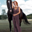 Beautiful young woman with a horse — Stock Photo