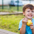 Little boy eating pear — Stock Photo