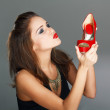Brunette woman holding red high heels — Stock Photo